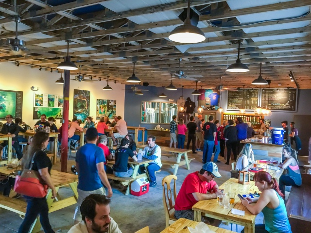 Visitors enjoy fresh craft beer inside the tasting room at First Magnitude Brewing Company in Gainesville Florida.
